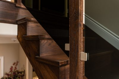 custom wood staircase with tinted glass railing